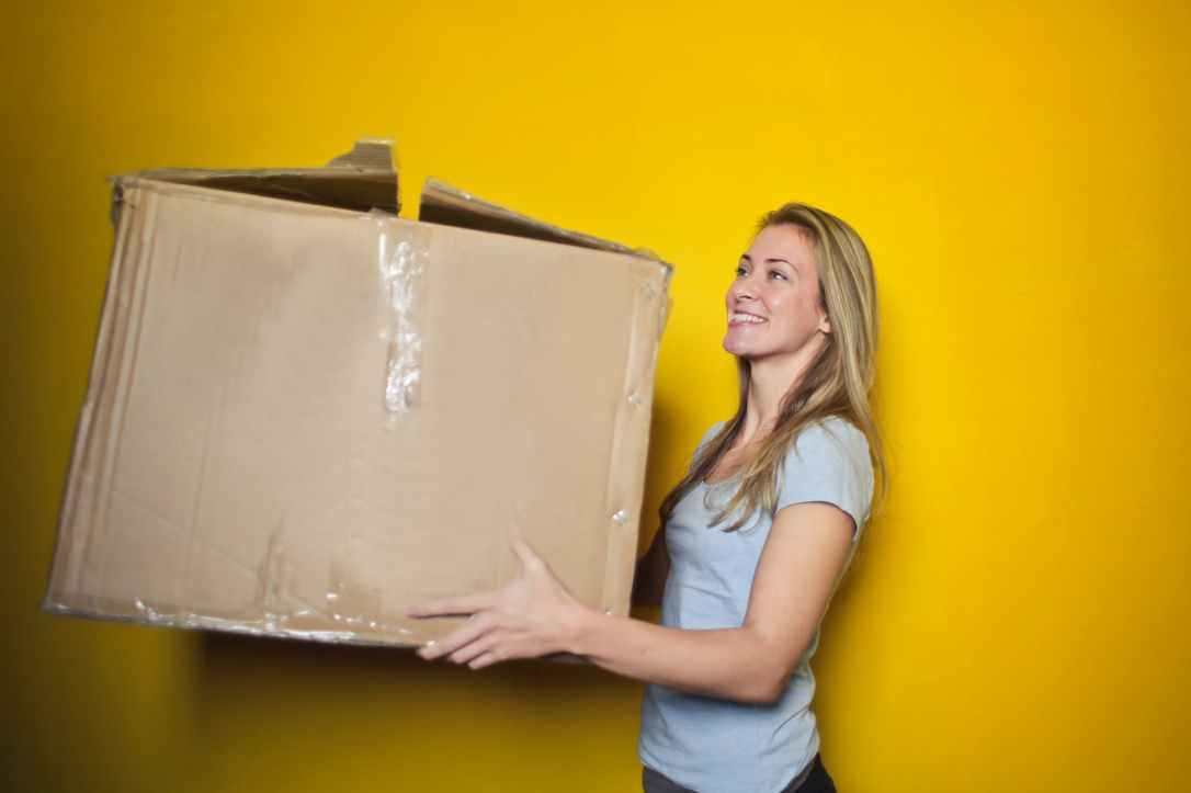 woman in grey shirt holding brown cardboard box